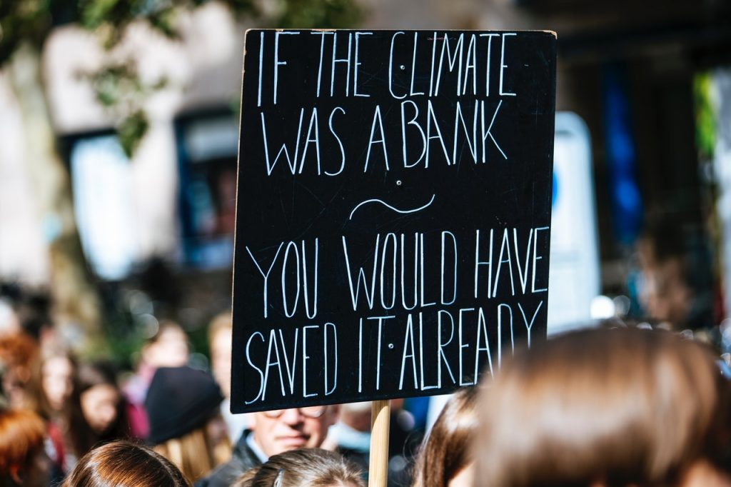 """A sign reading """"If the climate was a bank you would have saved it already."""""""