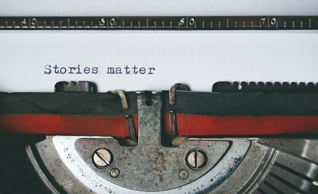 "Closeup of a typewriter with the text ""Stories matter"" written on a white piece of paper"