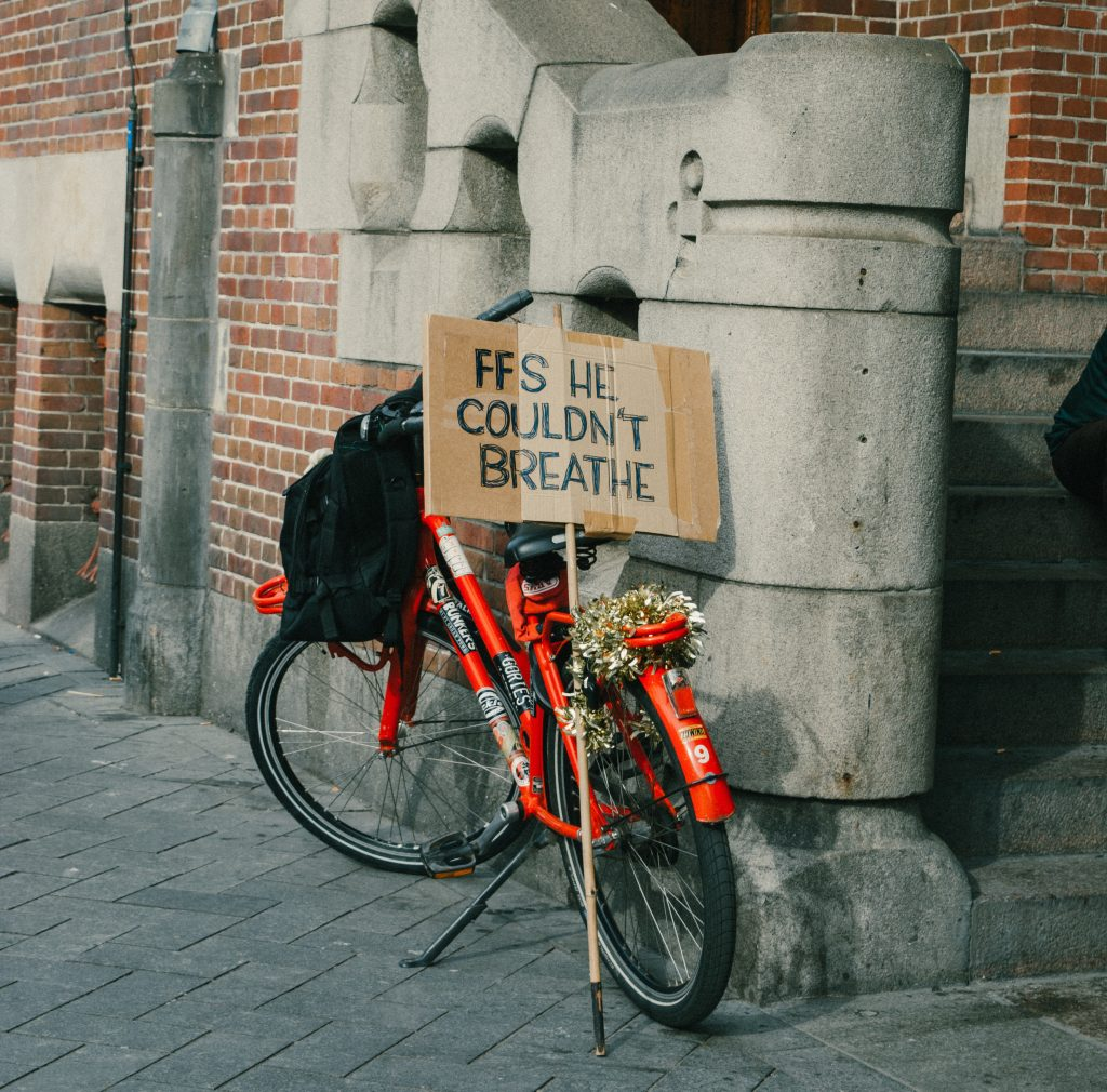 "An orange bicycle decked with flowers and a sign reading ""FFS He Couldn't Breathe"""